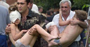 Dois homens carregam crianças resgatadas após a ação das forças russas em Beslan, em 2004 (arquivo). EFE